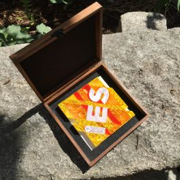 The quilled paper logo sits in a custom cigar box which I stained and lined with felt. I spray painted the hinges black.