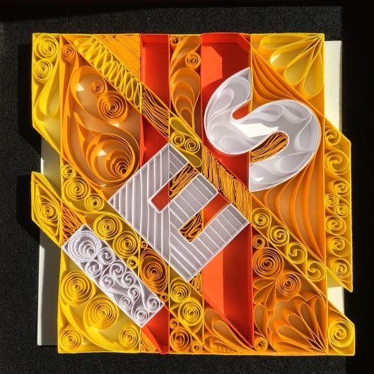 This is a quilled IES logo. The logo is constructed entirely of hand-cut paper and each piece was cut and glued by hand.